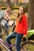 Cute happy teenage girl riding bicycles with her friends