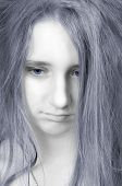 Beautiful sad teenage girl with pale face, blue hair and blue eyes