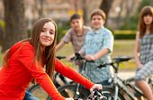 Beautiful teenage girl spending time with her friends riding bicycles