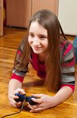 Happy teenage girl playing computer games using game controller
