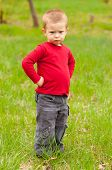 Cute angry little boy standing in the middle of the meadow on beautiful spring day