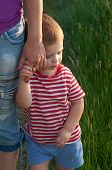 Cute little boy holding hand of his mother while walking on the meadow