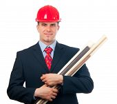 Handsome smiling engineer with hard hat on his head and blueprints in his arms isolated on white