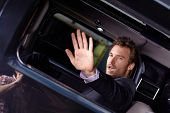 Celebrity sitting in luxury car, holding hand front of him, trying to avoid paparazzo to photographing.