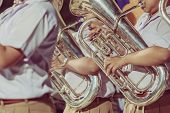 Male Student With Friends Blow The Euphonium With The Band For Performance On Stage At Night. poster