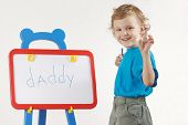 Little cute smiling boy wrote the word daddy on whiteboard