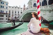 Woman Sitting Near Rialto Bridge In Venice Italy Looking At Grand Canal With Gondolas poster