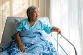Asian Depressed Elderly Woman Patients Lying On Bed Looking Out The Window In Hospital. Elderly Woma poster