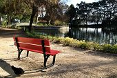 Red Bench Looking At The Pond With Ducks In The Idyllic Crystal Palace Garden In Oporto, Portugal poster