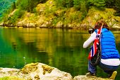 Female Tourist With Norwegian Flag On Fjord Shore, Taking Photo With Camera. Tourism And Traveling C poster