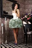 Luxury. Stylish Brunette Standing In Trendy Dress. Modern Interior