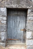 Old door with rusty hardware in stone building