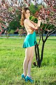 picture of leggy  - Pretty slim leggy woman wearing turquoise dress and shoes touching leaves of the tree - JPG