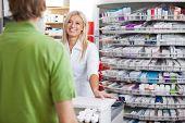 Pharmacist helping customer at counter