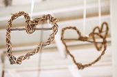 Wooden Weaved Hearts Hanging Off Roof Trusses At Wedding, Selective Focus
