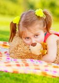 Closeup portrait of beautiful little girl having fun outdoors in spring time, lying down on green grass, hugging soft toy teddy bear