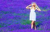 Cute blond teen girl standing on purple lavender meadow, woman wearing white dress and hat take sun bath on floral field