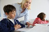Teacher looking at classbook with young boy