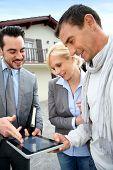 Real-estate-agent showing house plan on digital tablet