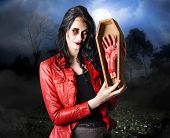 stock photo of exhumed  - Concept photograph of a female grave robber in terrifying makeup stealing human limbs and body parts - JPG