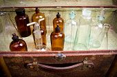 Vintage suitcase with chemical flasks and banks