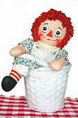 stock photo of rag-doll  - Old rag doll in a white wicker basket - JPG