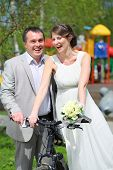 Happy newly married couple with a bicycle on the playground on a sunny day