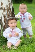 Little boy and girl in russian folk costumes near the birch in park