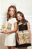 Portrait of luxury little girls with gold gift boxes