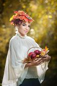 Autumn Woman. Girl with leaves in hair holding a basket with apples