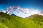 Beautiful alpine meadows at the foot of Mt. Shkhara. Dramatic overcast sky. Upper Svaneti, Georgia, Europe. Caucasus mountains. Beauty world.