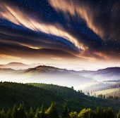 The Milky Way over the mountains landscape. Dramatic overcast sky. Carpathian, Ukraine, Europe. Beau