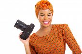 pretty african woman holding a digital SLR camera isolated on white