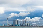 stock photo of belching  - three power plants in a large industrial harbor - JPG