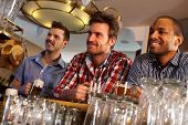 stock photo of mating  - Portrait of young men drinking beer at bar counter - JPG