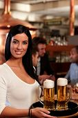 Beautiful young waitress in pub, holding beer mugs on tray, smiling.