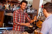 Portrait of young bartender serving beer in pub, looking at customer, smiling.