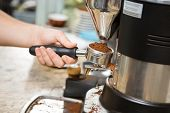 stock photo of coffee crop  - Cropped image of barista holding portafilter with ground coffee in cafe - JPG