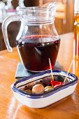 Sangria pitcher with plate of small tasty snacks on a table