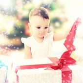 Holidays, baby girl opening box with presents, christmas, birthday, new year, x-mas concept - happy