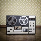 Old portable reel to reel tube tape-recorder is on obsolete parquet in retro room with vintage wallp