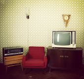 Vintage room with wallpaper, old fashioned armchair, retro tv, clocks, radio player and lamp. Toned