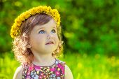 Portrait of a preschool girl with yellow flowers head wreath on