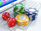 Online casino. Dices and chips on laptop. 3d