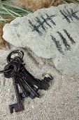Counting days by drawing sticks on stone with keys on sand background
