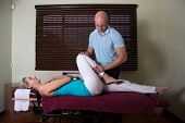 Chiropractor Stretching Female the  patient leg