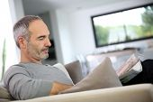 Senior man reading newspaper sit in couch