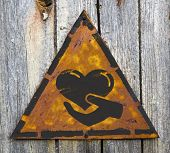 Charity Concept on Weathered Warning Sign.