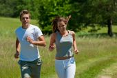 stock photo of woman couple  - Young man and woman running outdoors shallow DOF - JPG