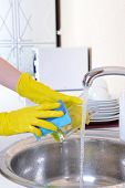 Close up hands of woman washing dishes in kitchen